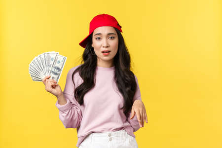 People emotions, lifestyle leisure and beauty concept. Unbothered cool and stylish rich girl in red cap, bragging about her wealth, showing money, careless spend cash, yellow background