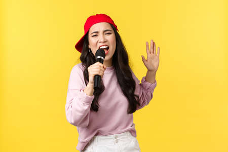 People emotions, lifestyle leisure and beauty concept. Carefree emotive young asian female hip hop singer in red cap, singing song in microphone with passion, yellow background