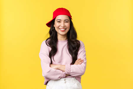 People emotions, lifestyle leisure and beauty concept. Happy cheerful asian woman smiling and laughing, cross arms chest, looking cool in hipster red cap over yellow background