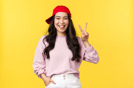 People emotions, lifestyle leisure and beauty concept. Carefree happy, asian hipster girl in summer cap, showing peace sign and smiling, enjoying sunny weekend over yellow background
