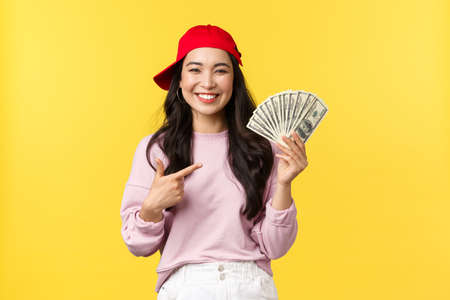 People emotions, lifestyle leisure and beauty concept. Happy attractive 20s woman in red cap, pointing at cash proudly. Satisfied asian girl tell how to earn money online, yellow background