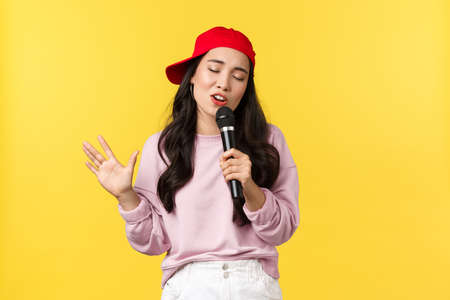 People emotions, lifestyle leisure and beauty concept. Cool and beautiful asian girl in red cap, close eyes and singing in microphone, performing on stage, standing yellow background
