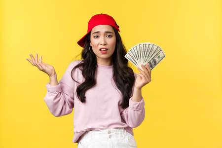 People emotions, lifestyle leisure and beauty concept. Unbothered cool and stylish rich girl in red cap, bragging about her wealth, showing money, careless spend cash, yellow background 免版税图像 - 151007253