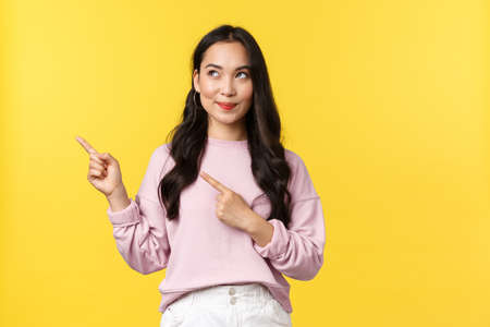 People emotions, lifestyle and fashion concept. Dreamy intrigued stylish girl found cool product in store, pointing fingers upper left corner, looking pleased and tempting, yellow background Standard-Bild