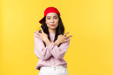 People emotions, lifestyle leisure and beauty concept. Cool and sassy stylish asian girl in red hip hop cap, showing swag gesture and smirk daring, standing confident over yellow background Standard-Bild