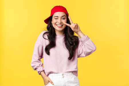 People emotions, lifestyle leisure and beauty concept. Cheerful teenage asian girl in hip hop red cap, wink and smiling broadly, showing peace sign, standing yellow background