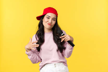 People emotions, lifestyle leisure and beauty concept. Stylish and cool young girl rapper in red cap, singing song and gesturing, performing with microphone, standing yellow background