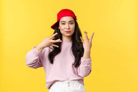 People emotions, lifestyle leisure and beauty concept. Stylish and cool, good-looking teenage korean girl in red cap, showing swag gesture standing yellow background