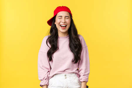 People emotions, lifestyle leisure and beauty concept. Happy carefree attractive asian woman having fun, enjoying summer vacation, laughing with closed eyes and amused expression