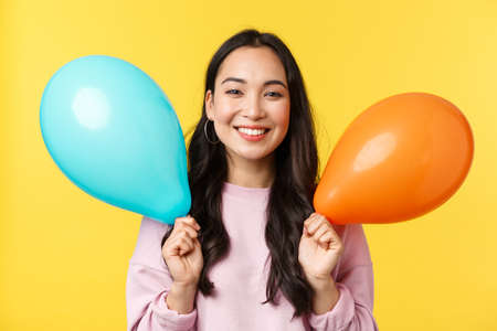 People emotions, lifestyle leisure and beauty concept. Happy cute asian birthday girl celebrating big event, holding balloons congratulating with holidays, standing yellow background