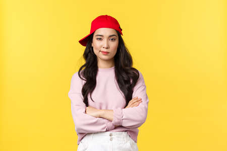 People emotions, lifestyle leisure and beauty concept. Serious-looking confident asian female in red cap, looking cool and sassy, cross arms chest determined, standing yellow background