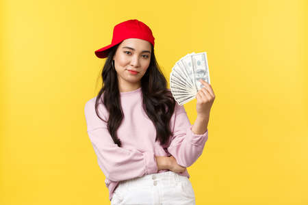 People emotions, lifestyle leisure and beauty concept. Sassy and confident, cool asian girl with lots of money, smiling determined, going shopping, ready to waste all cash, yellow background Standard-Bild