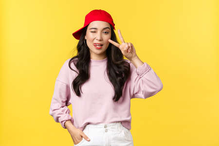 People emotions, lifestyle leisure and beauty concept. Stylish and cool asian girl in rnb red cap, showing peace sign and wink at camera, looking good in outfit over yellow background Standard-Bild