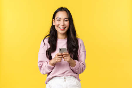 People emotions, lifestyle leisure and beauty concept. Happy and surprised pretty korean girl in stylish outfit, looking amazed with broad smile camera after reading great news in mobile appplication