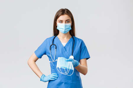Covid-19, preventing virus, health, healthcare workers and quarantine concept. Young doctor or female nurse in blue scrubs and protective equipment against coronavirus infection, give medical masks