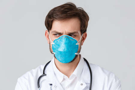 Hospital, healthcare workers, covid-19 treatment concept. Close-up of troubled and concerned doctor in medical respirator and scrubs, looking away with frowning face, feel nervous or upset, thinking Reklamní fotografie
