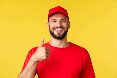 Close-up of cheerful, optimistic bearded employee, courier in red uniform, show thumbs-up, encourage clients order, provide best quality service, guarantee and support, yellow background 免版税图像 - 151011864