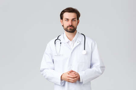 Hospital, healthcare workers, covid-19 treatment concept. Young doctor in scrubs making daily errands clinic, listening to patient symptoms, look camera, professional physician curing diseases Imagens