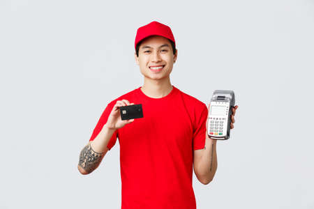 Smiling friendly courier in red uniform t-shirt and cap, advice pay for food delivery or orders with credit cards using payment terminal. Delivery guy show POS paying method, standing grey background