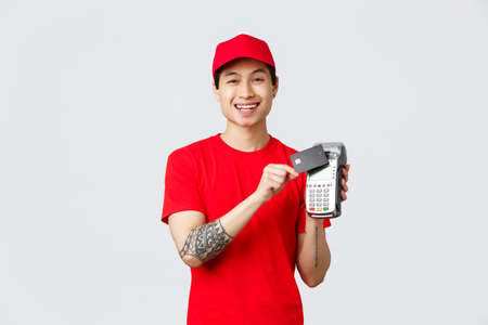 Smiling asian courier in red cap and t-shirt uniform, pressing credit card to payment terminal for contactless paying for client orders. Delivery guy explain method of pay, standing grey background