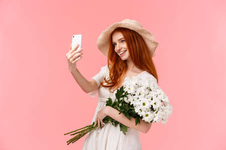 Celebration, social media and internet concept. Alluring sassy redhead female in straw hat, spring dress, holding bouquet, taking selfie on smartphone with white flowers, smiling pleased Reklamní fotografie