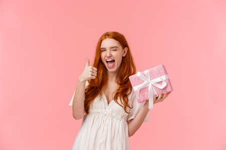 Waist-up portrait confident and happy, cheerful redhead girl celebrating birthday, show thumb-up in approval, like cool gift thanking friend, holding wrapped present as celebrating at party