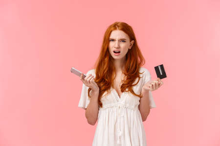 Frustrated and annoyed redhead girl feel displeased with strange online banking system, cant get clue what happened her order, holding smartphone and credit card squinting bothered Reklamní fotografie