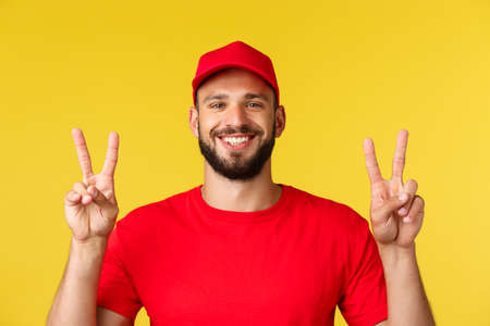 Close-up of cheerful, friendly courier, delivery guy in red t-shirt and cap, show peace signs and smiling, staying optimistic during covid-19 pandemic, standing yellow background 免版税图像 - 151012155