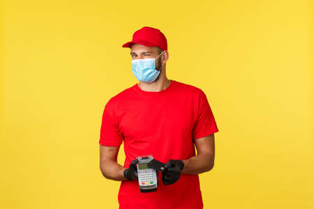 Food delivery, tracking, covid-19 and self-quarantine concept. Friendly courier in red uniform, medical mask and gloves, wink at camera, asking pay contactless with payment terminal and credit card