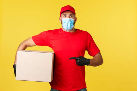 Express delivery during pandemic, covid-19, safe shipping, shopping concept. Shocked gasping courier staring camera speechless as pointing at box, carry package, wrong adress, yellow background Imagens