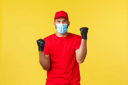 Express delivery during pandemic, covid-19, safe shipping, online shopping concept. Rejoicing cheerful courier in red uniform and medical mask, fist pump in celebration, winning, feel success