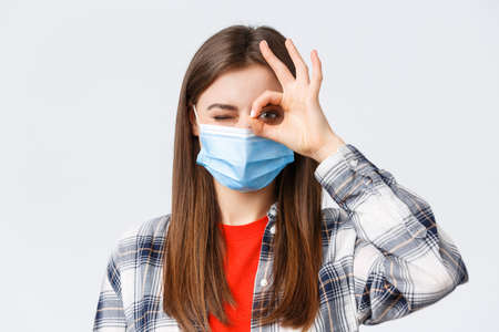 Coronavirus outbreak, leisure on quarantine, social distancing and emotions concept. Close-up of optimistic good-looking woman in medical mask show okay sign and wink 免版税图像 - 151089650