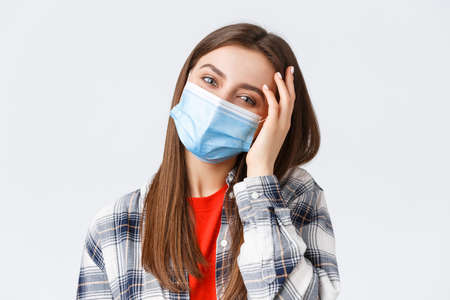 Coronavirus outbreak, leisure on quarantine, social distancing and emotions concept. Close-up of tender happy young woman in medical mask, tilt head, flirting and playing with hair 写真素材 - 151089652