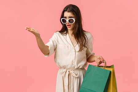 Such a raunch. Disappointed complaining young woman in dress and sunglasses, pointing and staring at something bad taste and awful, holding shopping bags, standing pink background.