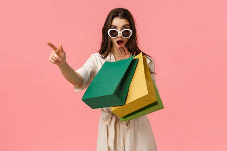 Shoppaholic, shopping and consumer concept. Excited and amused young brunette pretty woman checking out amazing discounts while strolling stores, holding bags, pointing left, gasping stunned.