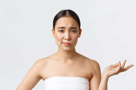 Beauty, cosmetology and spa salon concept. So what, i dont care. Indifferent skeptical asian woman in bath towel raising hand up careless and smirk unimpressed, white background 免版税图像