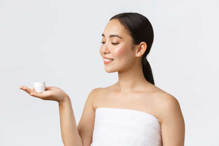 Beauty, personal care, spa salon and skincare concept. Close-up of beautiful asian woman in bath towel introduce facial cream, moisturizing or hydrating treatment for face, skin nourishing Banque d'images