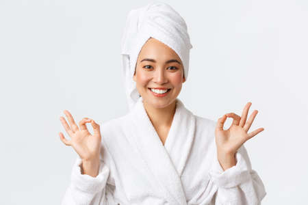 Personal care, women beauty, bath and shower concept. Close-up of relieved attractive asian woman attend spa beauty salon, wear bath towel and bathrobe, meditating, feeling nirvana, smiling