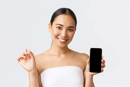 Beauty, personal and intimate care, mobile application concept. Attractive asian female in towel showing tampon and period, menstrual cycle period on smartphone app display, standing white background