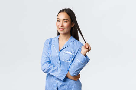 Tender gorgeous asian girl smiling dreamy at camera, standing in blue pajamas over white background. Woman prepare go to sleep in jammies, apply skincare products before bed