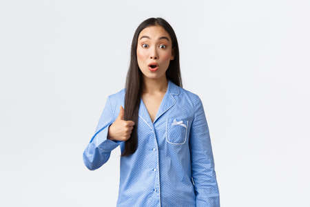 Impressed beautiful asian girl in blue pajamas showing thumbs-up and look amazed with great sleepover, awesome skincare product or promo. Woman showing support, recommend amazing thing