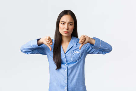 Disappointed frowning asian woman in blue pajamas express dislike, showing thumbs-down skeptical, judging bad product or skincare cosmetics, being displeased with quality, white background