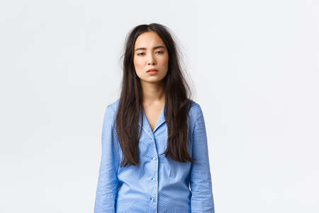 Exhausted asian woman with messy hair after lying in bed, wearing pajamas, looking tired with sleepy eyes as suffering insomnia, didnt have much sleep, waking up early, standing white background Stockfoto