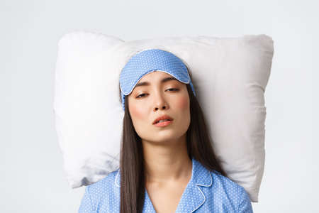 Close-up of exhausted sleepy asian girl looking tired as lying in bed on pillow, woman with insomnia problems have no sleep at night. Female waking up with hangover after sleepover party Banque d'images