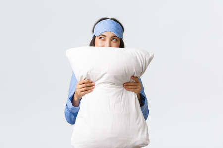 Dreamy asian girl in sleeping mask and blue pajamas hugging pillow and looking cunning at upper left corner, imaging something, having idea in comment bubble, standing white background