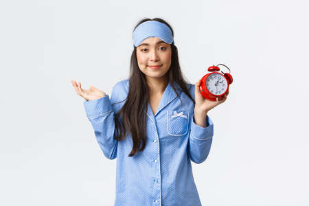 Unbothered cute asian girl in sleeping mask and pajamas showing alarm clock and shrugging careless, overslept but dont give damn, dont care for being late, standing white background