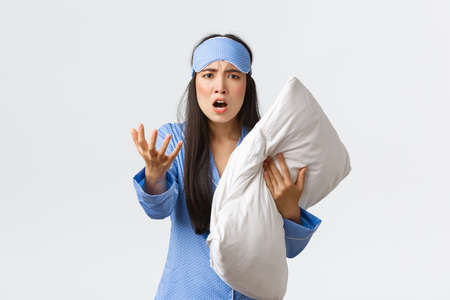 Angry bothered asian girl with insomnia, wearing sleeping mask and pajama, looking pissed-off as holding pillow and shaking hand furious, complaining on noise at night, white background Stockfoto