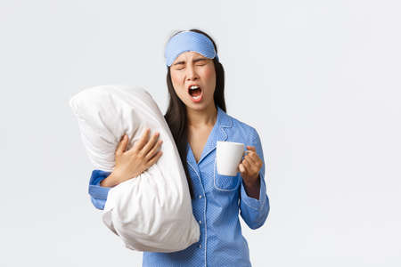 Morning lifestyle, breakfast and people concept. Girl with insomnia in sleeping mask and pajamas, hugging pillow, drinking coffee and yawning, trying wake-up, white background Foto de archivo