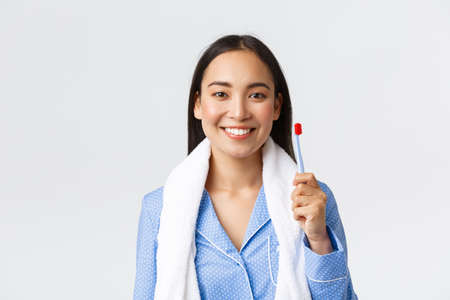 Daily routine, morning and hygiene concept. Pretty asian girl in blue pajama, holding towel and showing toothbrush, smiling white teeth, getting ready shower before bed, white background Reklamní fotografie