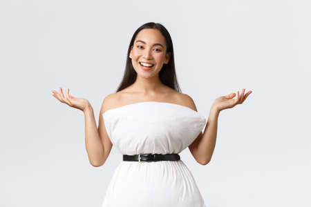 Gorgeous smiling and creative asian woman create dress from pillow cinching with belt around waste raising hands up and grinning, showing her new outfit, standing white background Imagens
